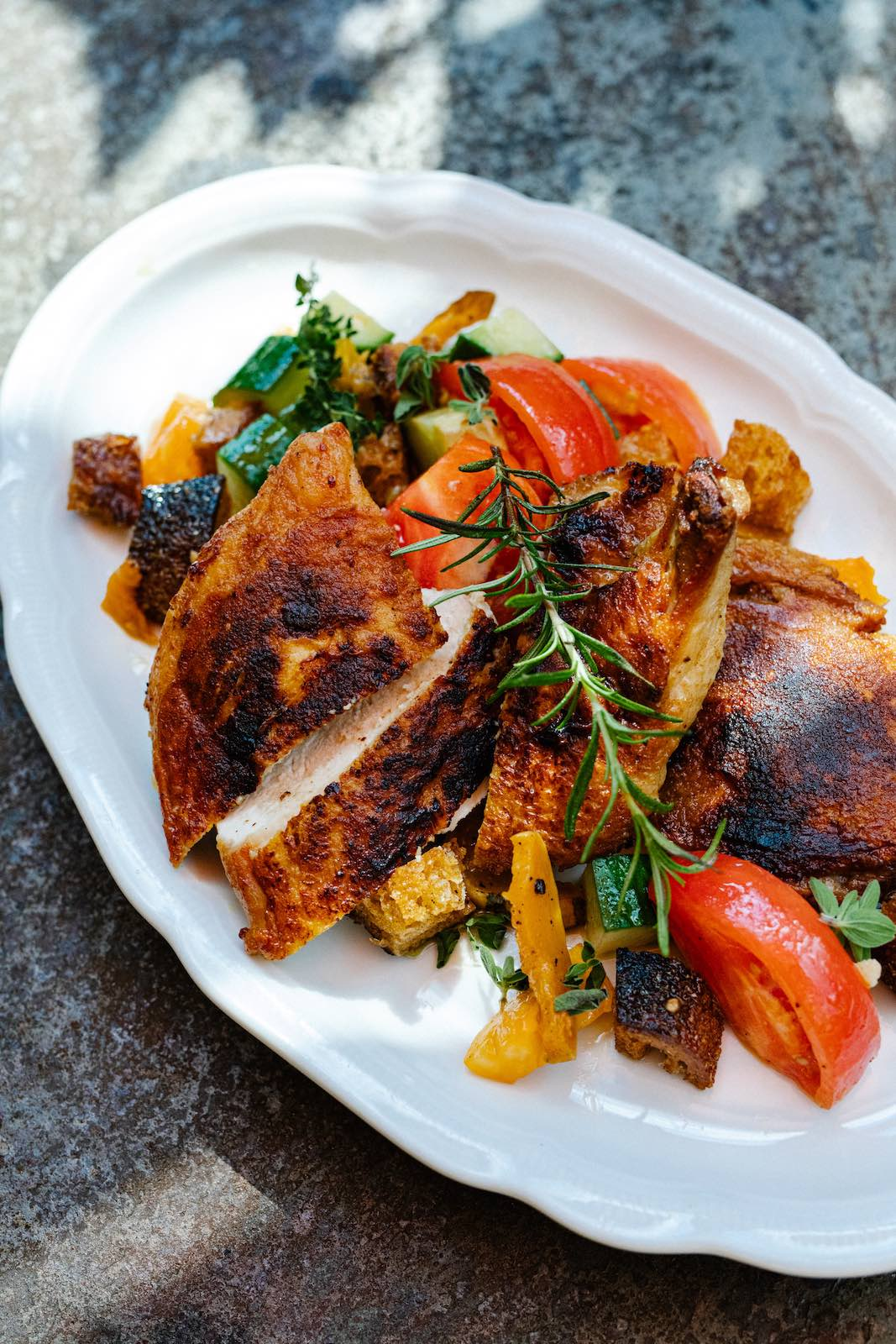A bright panzanella accompanies the  pollo al mattone at Osteria Georgi